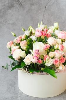 Piwonie, róże i eustomy w papierowym pudełku upominkowym