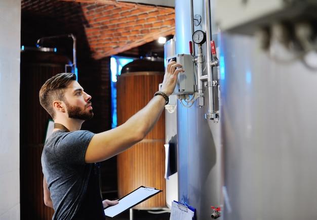 Piwowar na tle zbiorników piwa dokonuje obliczeń