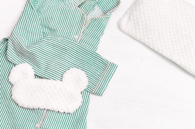 Piżama dla dziewczynek, maska do spania, miękka puszysta poduszka na białym drewnie.