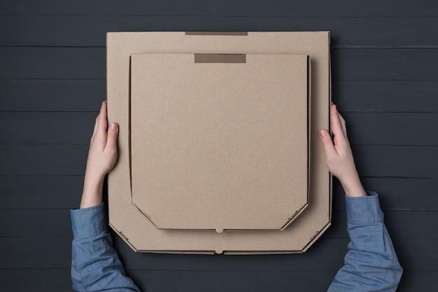 Pizza boksuje w children rękach na czarnym tle.