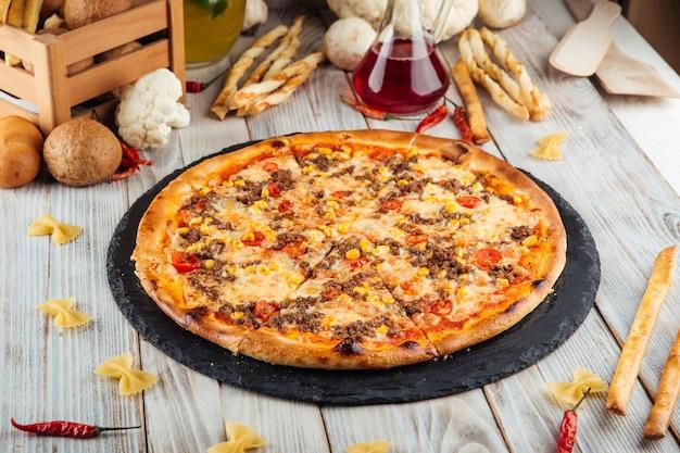Pizza bolońska z mieloną kukurydzą wołową i pomidorami