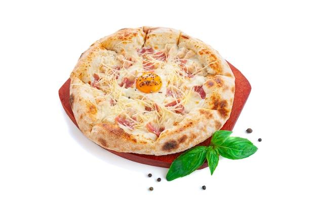 Pizza carbonara z boczkiem. na drewnianej desce. ozdobiony bazylią i przyprawami. widok z góry. białe tło.