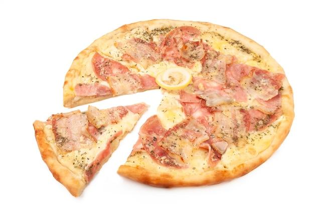 Pizza carbonara. z parmezanem, mozzarellą, boczkiem, szynką, oregano i cytryną. kawałek jest odcięty od pizzy. białe tło. odosobniony. zbliżenie.
