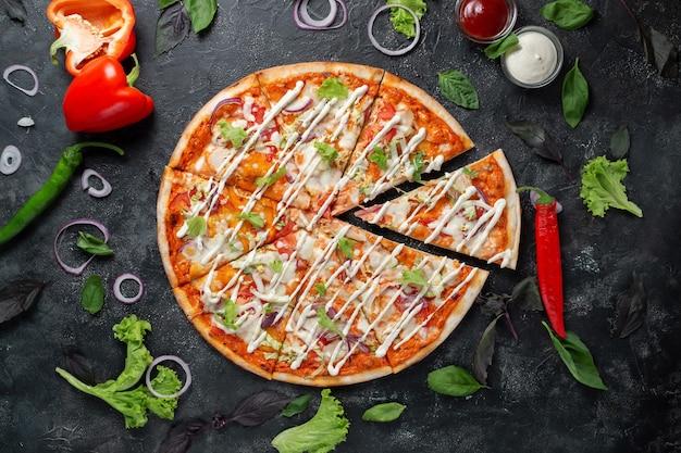 Pizza cezar na ciemnym tle z warzywami, papryką, mozzarellą i bazylią. widok z góry na ciemny kamienny stół