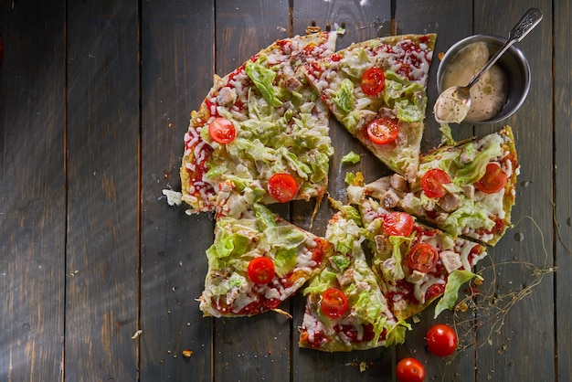 Pizza cezar, oliwa z oliwek, kurczak, sałata lodowa, sos cezar, pomidory koktajlowe, oliwki i parmezan na drewnianym stole. widok z góry