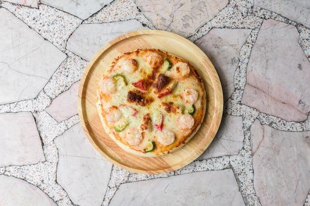 Pizza domowej roboty na marmurowym stole, widok z góry zbliżenie.