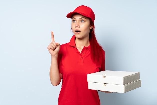 Pizza doręczeniowa dziewczyna trzyma pizzę nad odosobnioną ścianą myśleć pomysł wskazuje palec up