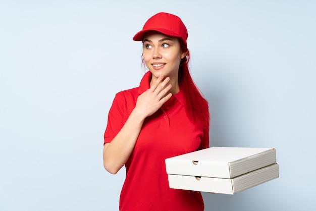 Pizza doręczeniowa kobieta trzyma pizzę nad odosobnioną ścianą przyglądającą up podczas gdy ono uśmiecha się