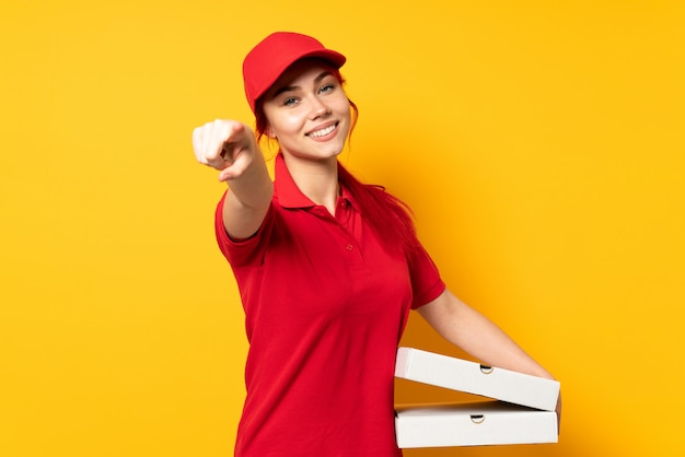 Pizza doręczeniowa kobieta trzyma pizzę nad odosobnionym ściennym wskazuje przodem z szczęśliwym wyrażeniem