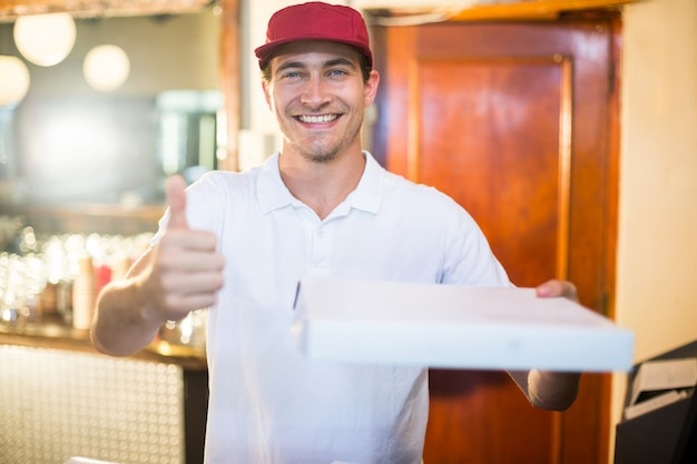 Pizza doręczeniowy mężczyzna trzyma pizzy pudełko gestykuluje aprobaty