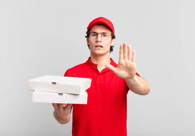 Pizza dostarcza chłopca wyglądającego poważnie, surowo, niezadowolonego i wściekłego, pokazując otwartą dłoń, wykonując gest zatrzymania