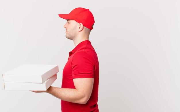 Pizza dostarcza człowieka w widoku profilu, który chce skopiować przestrzeń do przodu, myśląc, wyobrażając sobie lub marząc na jawie