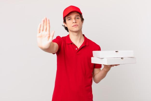 Pizza dostarcza mężczyzna wyglądający poważnie pokazując otwartą dłoń robiący gest zatrzymania
