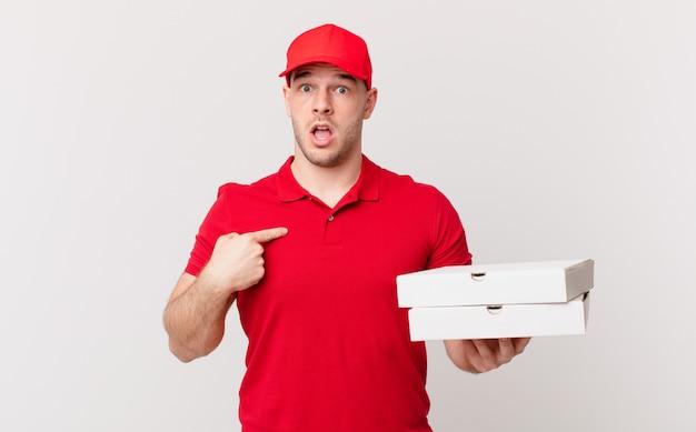 Pizza dostarcza mężczyzny, który wygląda na zszokowanego i zaskoczonego z szeroko otwartymi ustami, wskazując na siebie