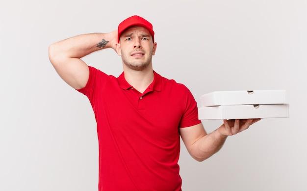 Pizza dostarcza mężczyzny zestresowanego, zmartwionego, niespokojnego lub przestraszonego, z rękami na głowie, panikującego z powodu błędu