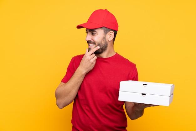 Pizza dostawa człowiek w mundurze roboczym, zbierając pudełka po pizzy na pojedyncze żółte ściany myśląc pomysł i patrząc na bok