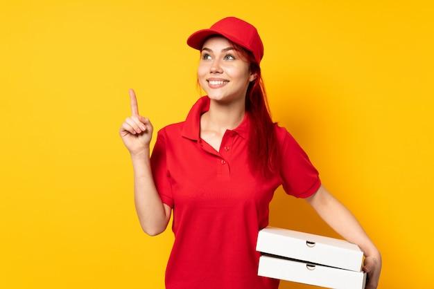 Pizza dostawa kobieta trzyma pizzę nad izolowaną ścianą, wskazując na świetny pomysł