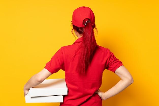 Pizza dostawy kobieta trzyma pizzę na pojedyncze ściany w tylnej pozycji