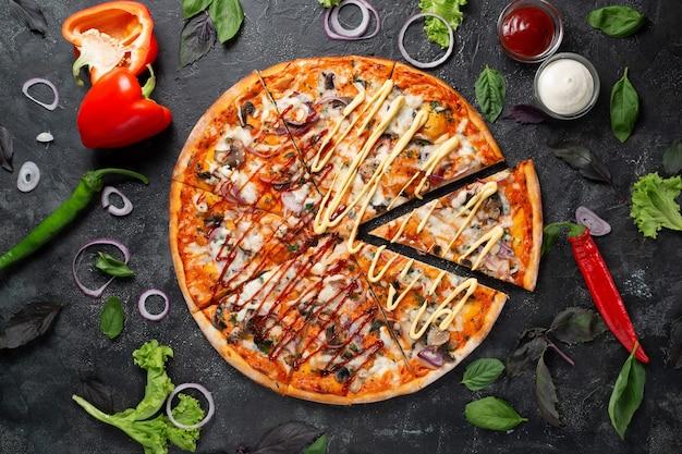 Pizza grillowa na ciemnym tle z warzywami, papryką, mozzarellą i bazylią. widok z góry na ciemny kamienny stół