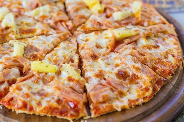 Pizza hawajska to włoskie jedzenie, które przyrządza się z sosu pomidorowego, posiekanego ananasa, szynki i sera.