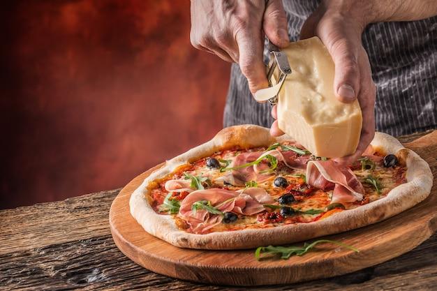 Pizza i szef kuchni. szef kuchni w restauracji przygotowuje pizzę i ozdabia ją parmezanem.