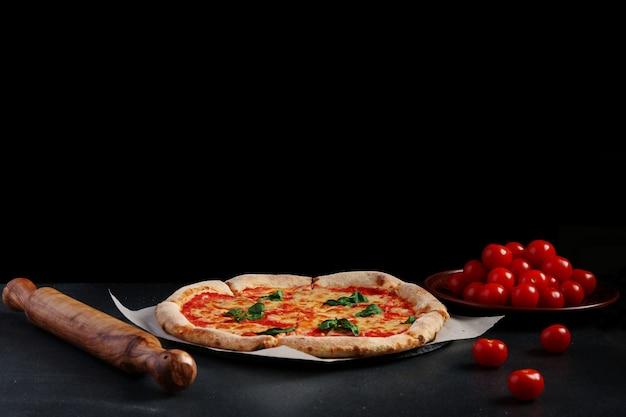 Pizza margarita i wiśnie pomidorowe na ciemnym tle