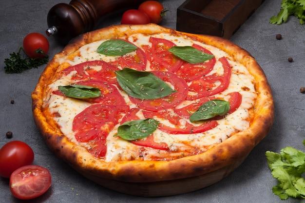 Pizza margarita z pomidorami, mozzarellą na szarym tle