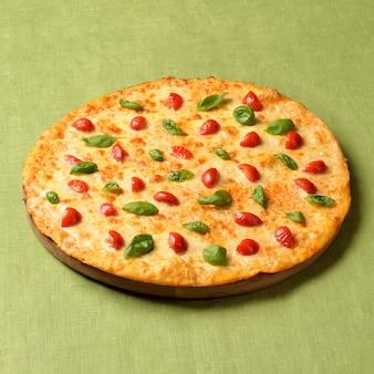 Pizza margharita na zielonym lnianym tle. popularne fast foody na całym świecie.