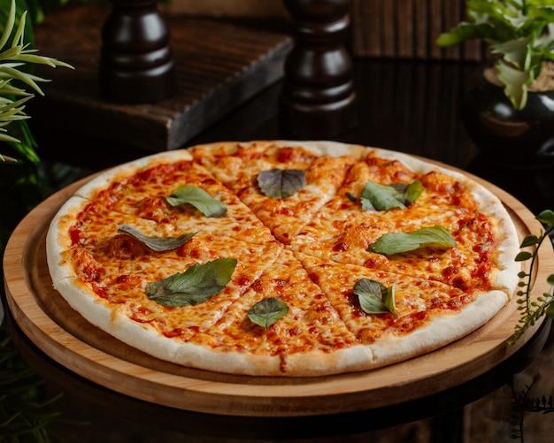 Pizza margharita z pełnym sosem pomidorowym i zielonymi liśćmi bazylii na plasterek