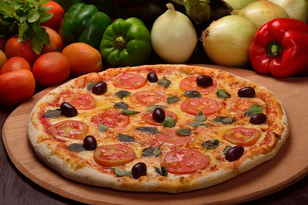 Pizza margherita z czarnymi oliwkami na desce i warzywami w tle.