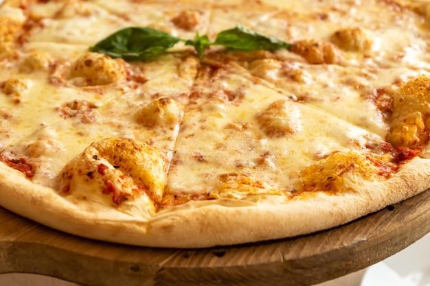 Pizza margherita z mozzarellą i liśćmi bazylii na drewnianym blacie.