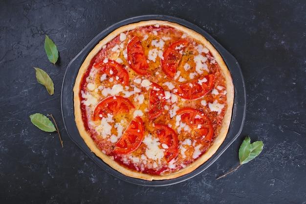 Pizza margherita z serem i pomidorami na ciemno