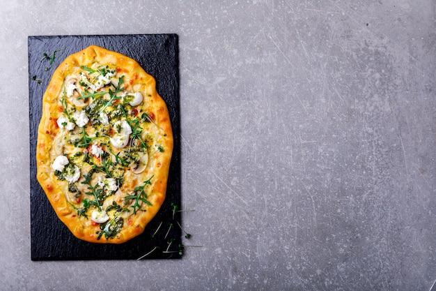 Pizza mozzarella z pieczarkami rukolą z sosem pesto