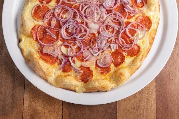 Pizza na brązowym drewnianym stole