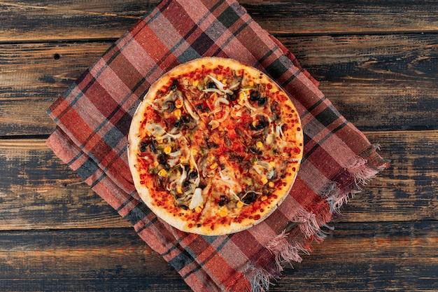 Pizza na ciemnym tle drewniane i piknikowe tkaniny. poziomy