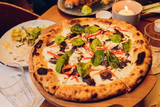 Pizza na cienkim cieście ze świeżymi liśćmi bazylii. kawałki pizzy