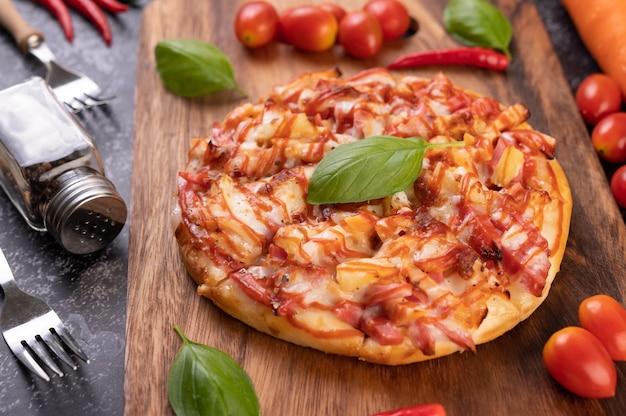 Pizza na drewnianej tacy z pomidorami chili i bazylią.