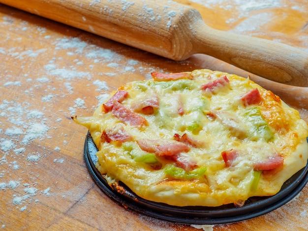 Pizza na drewnianym stole posypana mąką