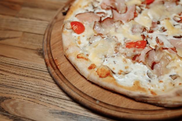 Pizza na drewnianym stole widok z góry. fast food. publikuj bloga w mediach społecznościowych. z miejsca na kopię. pizza gotowa do spożycia.