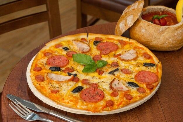 Pizza na kuchennym stole z widelcem i sosem