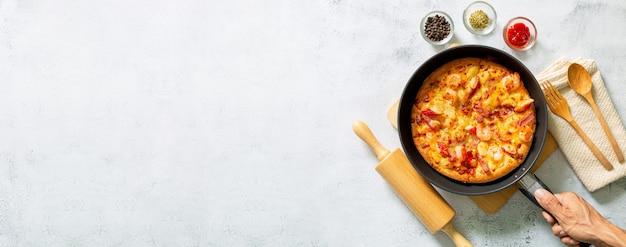 Pizza na patelni świeża surowa pizza z pieczarkami pomidorkami koktajlowymi bazylia i parmezan w rundzie