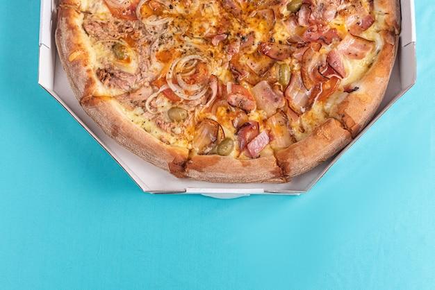 Pizza na stole w jasnoniebieskim kolorze