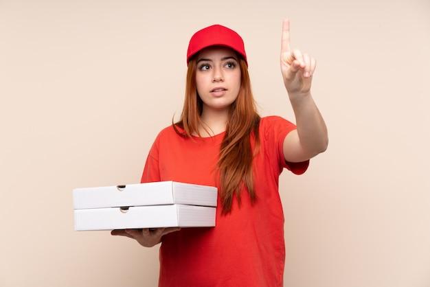 Pizza nastolatek dostawy dziewczyna trzyma pizzę na na białym tle ściany dotykając przezroczystego ekranu