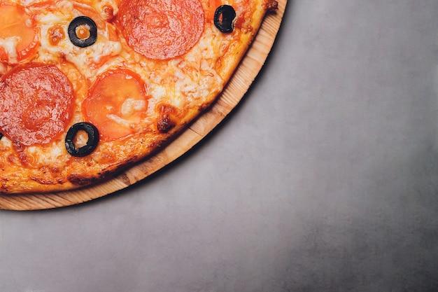 Pizza pepperoni, mozzarella, oregano na czarnym tle.