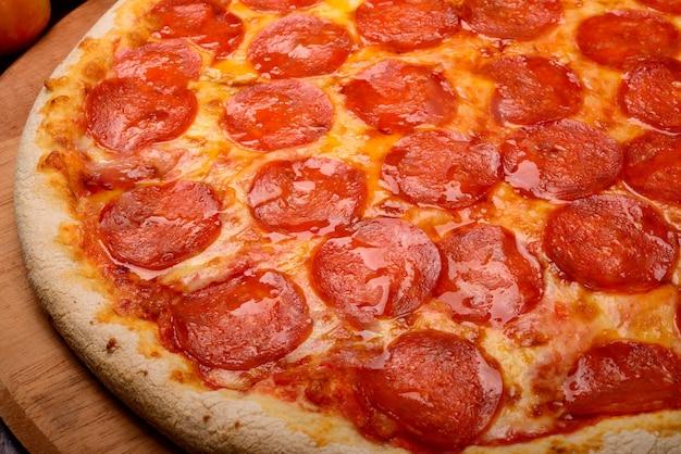 Pizza pepperoni na desce i warzywa w tle