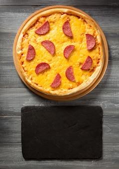 Pizza pepperoni na drewnianym stole