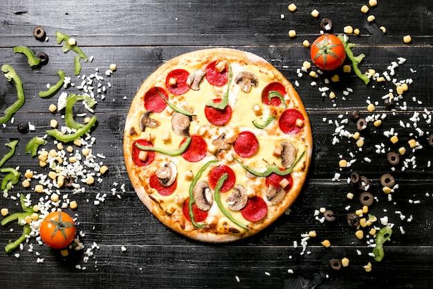 Pizza pepperoni z grzybami obok sera posypuje pomidorową papryką kukurydzianą
