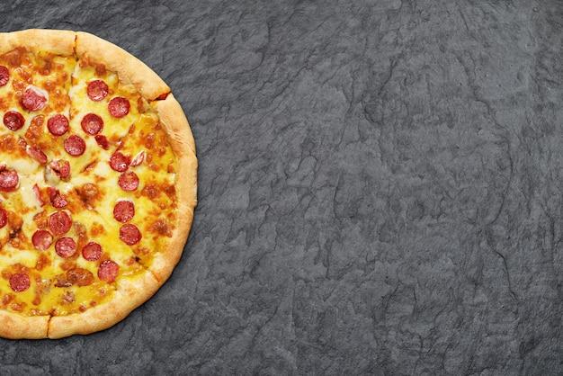 Pizza pepperoni z kiełbaskami, sosem pomidorowym i serem na czarnym tle łupków.