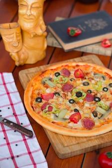 Pizza pepperoni z papryką, plasterkami pomidorów, grzybami i oliwkami.