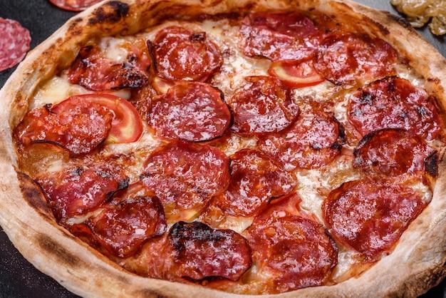 Pizza pepperoni z sosem do pizzy, serem mozzarella i pepperoni. pizza na stole z dodatkami